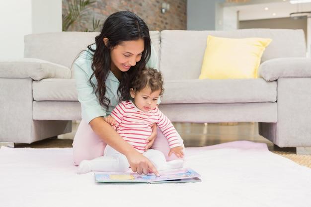 リビングルームでカーペットの上の本を見て彼女の赤ちゃんと一緒に幸せな母