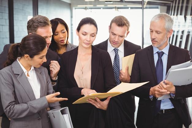 文書を見て、ビジネスマンとやり取りする弁護士