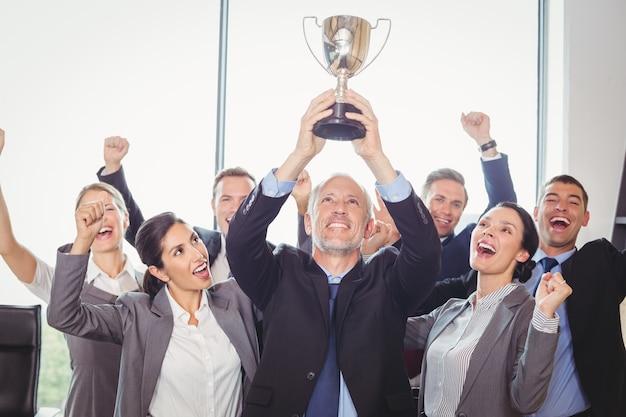 トロフィーを保持しているエグゼクティブと勝利のビジネスチーム