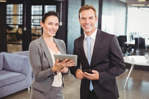 幸せなビジネスの男性とデジタルタブレットと携帯電話を持つ女性実業家