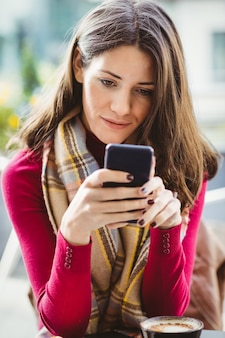女性が彼女のスマートフォンを使用して