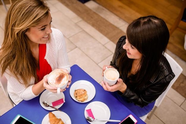 コーヒーとスナックを飲みながら話している女性