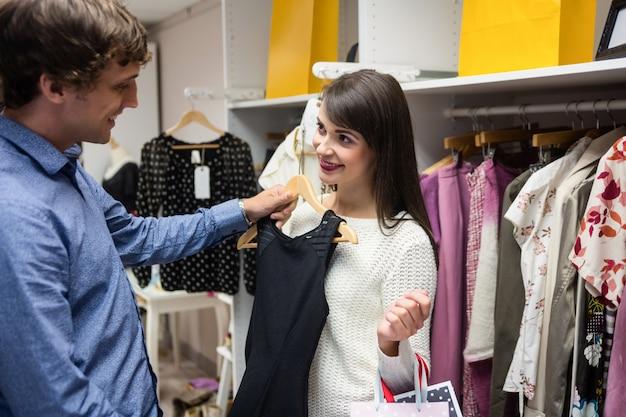 服を買いながらドレスを選択するカップル