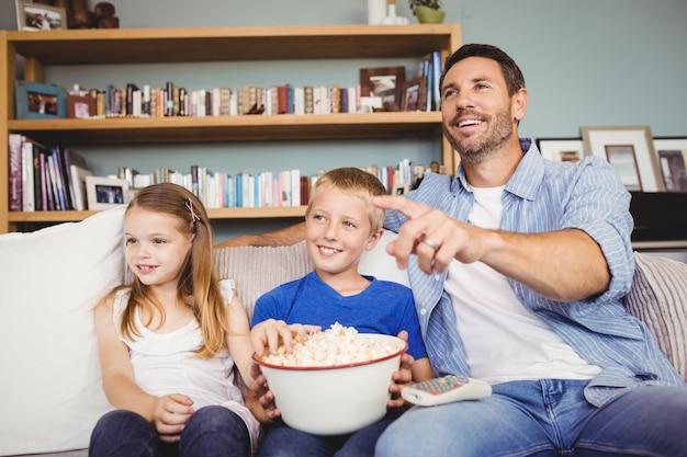 テレビを見ながらポップコーンと幸せな家族