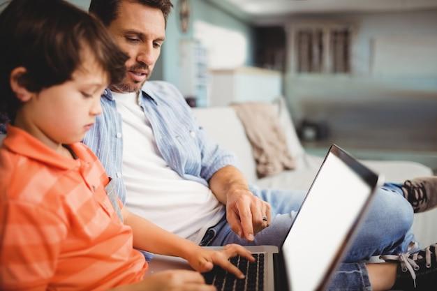 父と息子のソファに座ってラップトップに取り組んで