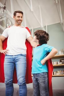 スーパーヒーローの衣装で陽気な父と息子