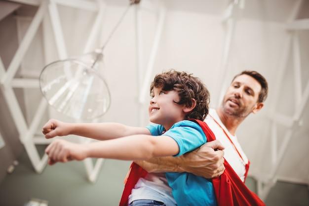 スーパーヒーローの衣装を着て陽気な息子を持つ父親の低角度のビュー