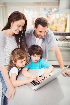 テーブルでのラップトップに取り組んで幸せな家族