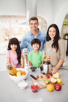 フルーツジュースを準備する笑顔の家族の肖像画