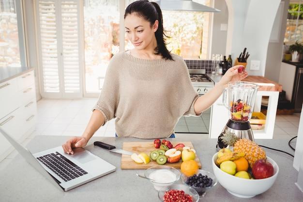 ラップトップに取り組んでいる間フルーツジュースを準備する女性