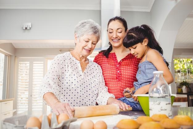 Старшая женщина готовит еду с семьей