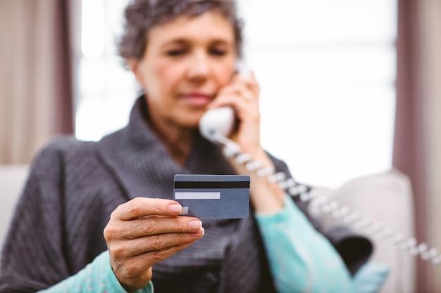 電話で話しながらクレジットカードを保持している成熟した女性