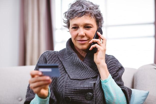 携帯電話で話しながらクレジットカードを保持している成熟した女性