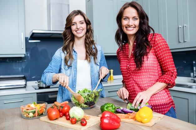 野菜サラダを準備する女性の友人を笑顔の肖像画
