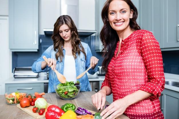 野菜サラダを準備する幸せな女性の友人