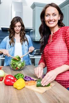 Счастливые подруги готовят овощной салат