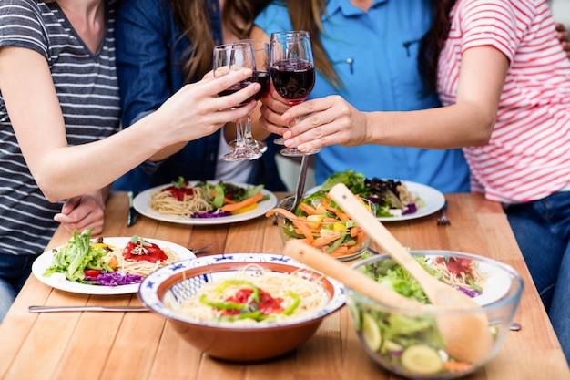 赤ワインのグラスを乾杯の友人の中央部