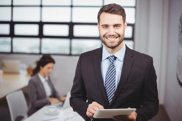 Бизнесмен используя цифровую таблетку пока коллега в предпосылке