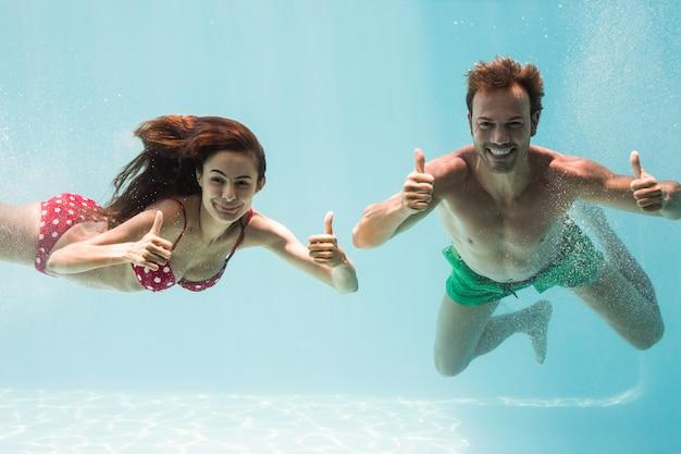 Улыбаясь пара показывает палец вверх во время купания