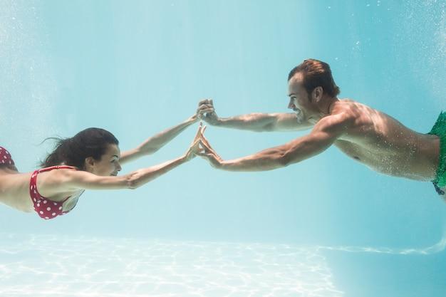 水中泳いでいる間手を繋いでいるカップル