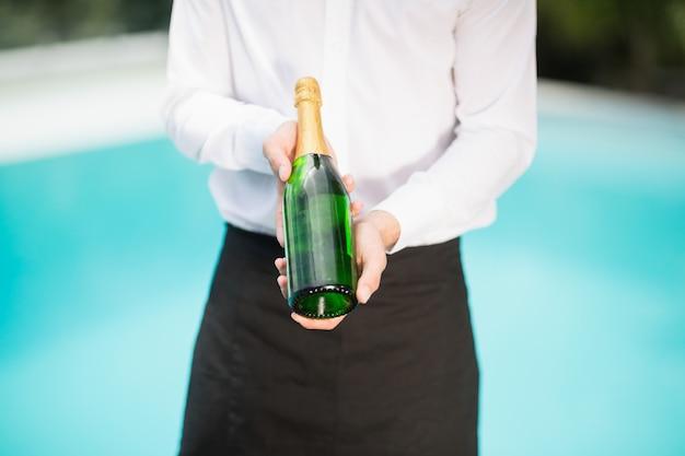 シャンパンのボトルを保持しているウェイターの中央部