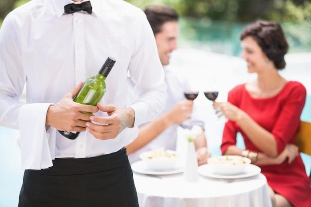 ワインのボトルを保持しているウェイターの中央部