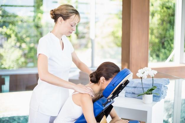 肩のマッサージを受ける若い女性