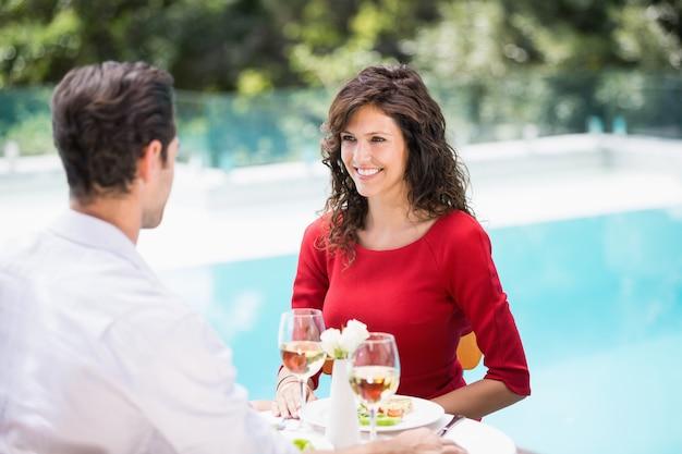 スイミングプールのそばに座って笑顔のカップル
