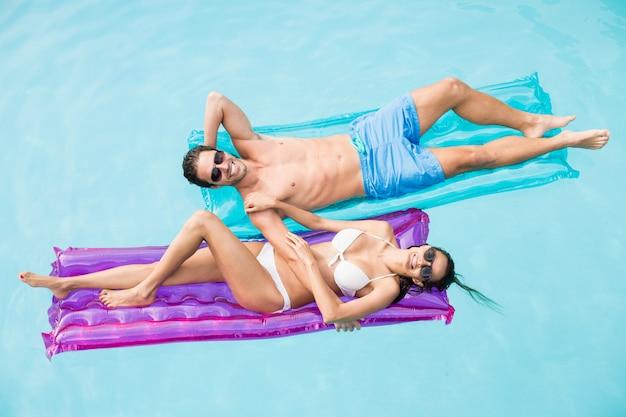 Веселая пара отдыхает на надувном плоту