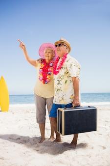 Пожилая пара держит чемодан