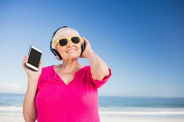 年配の女性がヘッドフォンで音楽を聴く