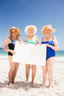 Старшие женщины друзья, держа чистый лист бумаги
