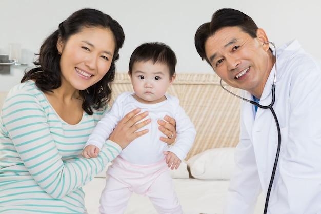 医者、母親と赤ちゃんがベッドの上の肖像画