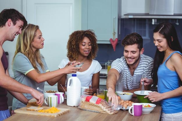朝食のテーブルに立っている幸せな友達
