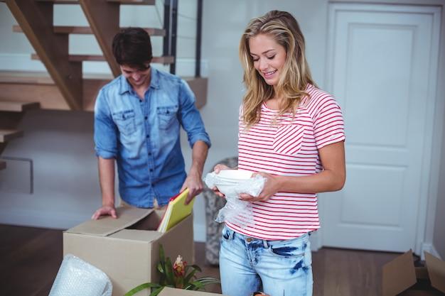 Улыбающаяся женщина распаковывает миски из коробки с мужчиной