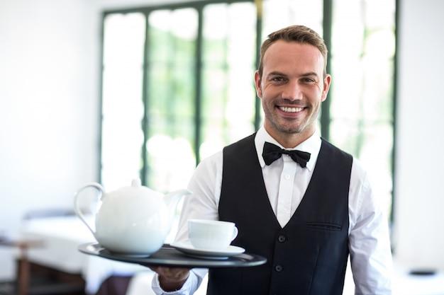 Официант, улыбаясь в камеру