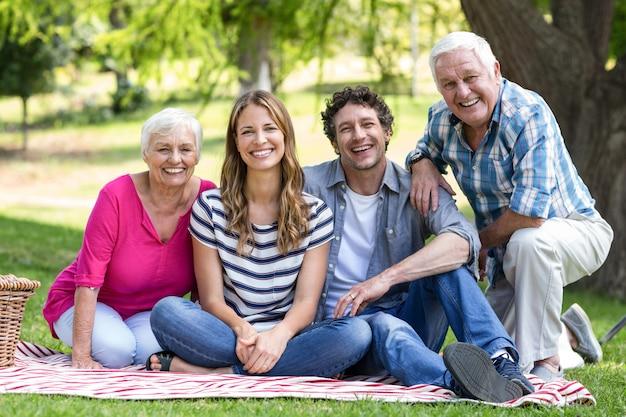 毛布の上に座って笑顔の家族