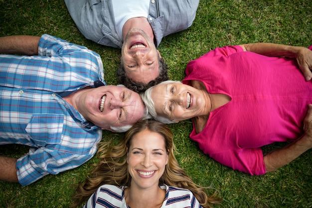 草で横になっている笑顔の家族
