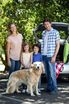 車の前に立っている笑顔の家族