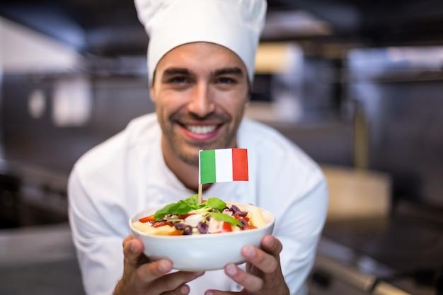 イタリアの旗と食事を提示するハンサムなシェフ