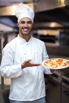 ピザを提示するハンサムなシェフ