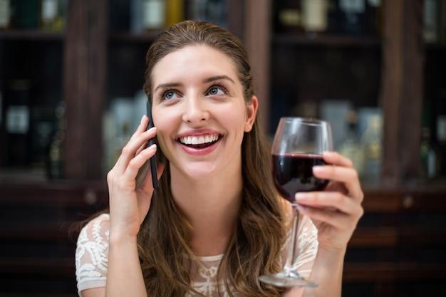 電話で話しながらワイングラスを保持している陽気な女性