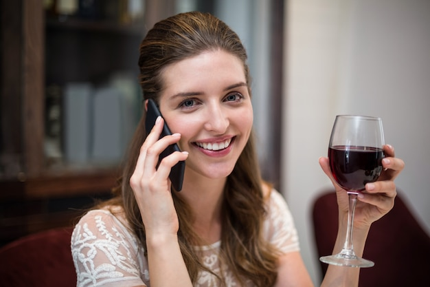 電話で話しながらワイングラスを保持している女性の肖像画