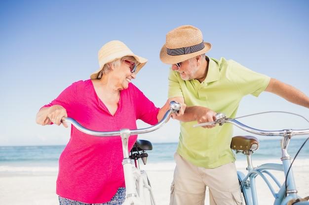 自転車に乗る年配のカップルを笑ってください。