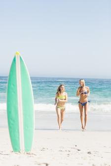 Доска для серфинга в песке и две женщины, бегущие по пляжу