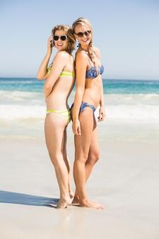 Две счастливые женщины в бикини и солнцезащитные очки стоят спиной к спине