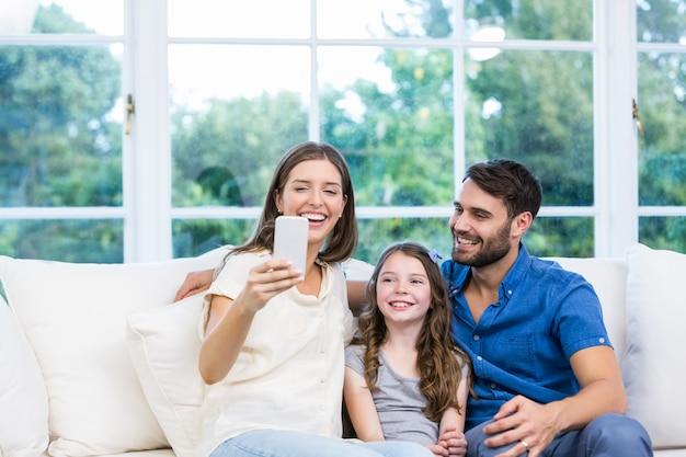 家族と一緒に座ってスマートフォンを見ている女性