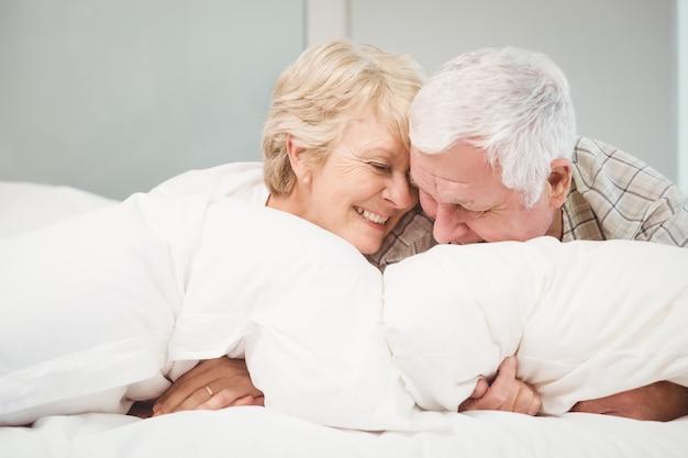 ベッドで休んで遊び心のある年配のカップル
