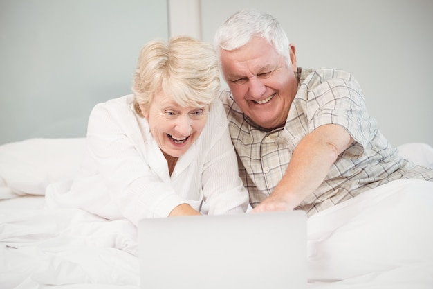 Пара смеется, используя ноутбук в постели