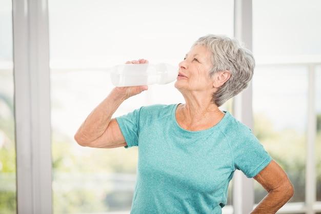 年配の女性は水を飲む